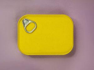 Yellow Aluminium sardine can against a purple background